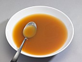 A bowl of chicken broth with a spoon