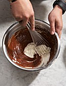 Cream being mixed into melted chocolate with a whisk in a metal bowl
