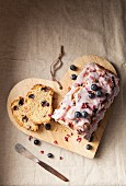 A sliced blueberry loaf cake with icing and dried rose petals