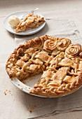 Apple Pie mit Teiggitter und Teigrosen in der Form, angeschnitten