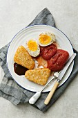 A vegetarian English breakfast with hash browns, tomatoes and eggs