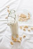 Homemade vegan cashew milk in a glass bottle