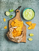 Mexican corn chips and fresh guacamole sauce on wooden serving board over grey concrete table background, top view, vertical composition