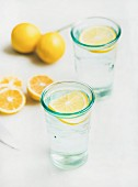 Morning detox lemon water in glasses served with fresh lemons over light grey marble background, selective focus. Clean eating, weight loss, healthy, detox, dieting concept
