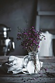 Blütenzweige in Glaskrug auf rustikalem Tisch in Landhausküche