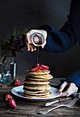 Woman pouring maple syrup on the pancakes with strawberries