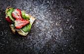 Brot belegt mit Frischkäse, Blattsalat und Erdbeeren (Aufsicht)