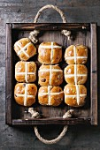 Hot cross buns in wooden tray over old texture metal background