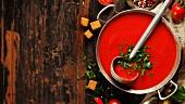 Hausgemachte Tomatencremesuppe mit Suppenkelle im Kochtopf (Aufsicht)