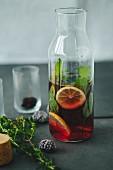 Aromatisiertes Wasser mit Beeren, Kräutern und Zitronen in Glasflasche