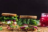 Feta-Sandwich mit Avocadocreme, Zwiebeln, Rucola und Gurken