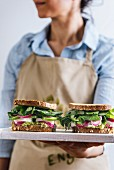 A woman with a blue shirt and a beige apron holding springtime feta sandwiches with herbs, avocado and pickled red onions