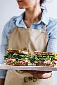 Frau mit Schürze serviert Feta-Sandwiches mit Rucola, Avocado und Zwiebeln