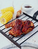 Half a BBQ chicken on a grill tray, with corn cobs and BBQ sauce