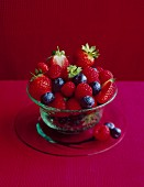 Fresh berries in a glass bowl on a pink tablecloth against a red background