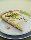 A slice of lemon tart with lime zest and coconut chips