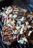 T-bone steak with onions and blue cheese on a grill