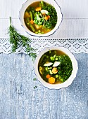 Vegan green minestrone soup with zucchini, cabbage, broccoli, beans and dill (top view)