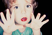 A child with a red smeared mouth and stained fingers