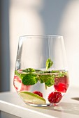 A glass of water flavored with raspberries, lime and mint