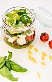 Pasta salad with pesto, tomatoes, mozzarella, rocket and basil in a glass jar