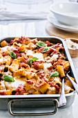 Pasta bake with ragout, mozzarella and bechamel sauce in a baking dish