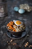 An Asian bowl with noodles, vegetables, mushrooms, cashew nuts and fried eggs (Asia)