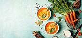 Carrot soup in white bowls on blue background