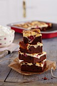 Several pieces of cherry and chocolate cake, stacked