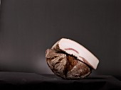 Half a loaf of bread and a piece of white bacon in front of a black background