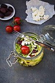 Zoodles (zucchini noodles) in a glass jar with tomatoes, feta and olives