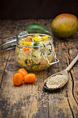 Quinoa salad with avocado, cucumber, tomato and mango in a glass jar