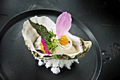 An oyster being decorated with flower petals