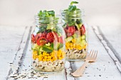 Rice salad in a glass jar with wild rice, sweetcorn, cucumber, tomato and lamb's lettuce