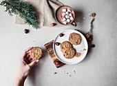 Glutenfreie Kekse auf Teller, dahinter Tasse heiße Schokolade mit Marshmallows