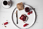 Bread and jam on a white wooden board with a cup of coffee (seen from above)
