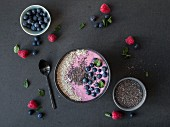 A pink smoothie bowl with berries and gluten-free millet flakes (seen from above)