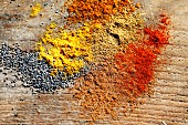Various spices and poppyseeds on a wooden surface