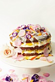 Layered lemon drizzle cake decorated with icing and edible flowers