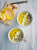 Yellow mango and banana smoothie bowls with turmeric