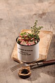 Sausage salad with radishes and thyme in an enamel mug