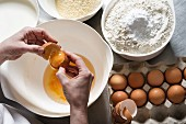 Hands breaking eggs over a bowl with almond flour and regular flour with baking powder next to it