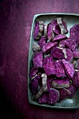 Sliced ​​purple sweet potatoes on a metal tray