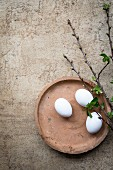 An arrangement of eggs and twigs on a clay plate for Easter