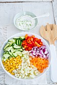 Chopped vegetables in a bowl with a dish of yoghurt and dill dressing next to it