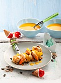 A scallop skewer with orange fillets and pumpkin sauce