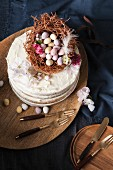 A naked sponge cake decorated with an Easter nest, chocolate eggs, and blossoms