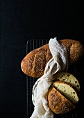 Italian semolina bread on a cooling rack against a black background