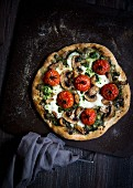 A vegetarian pizza with tomatoes, mushrooms, pesto and mozzarella