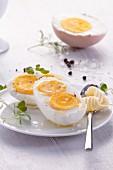 Halbes gekochtes Ei mit zwei Eigelben, Salz und Butter